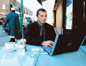 Network down: A man uses Wi-Fi access at a cafe in Brick Lane, London. Experts say municipal Wi-Fi networks haven't taken off in most parts of the world, with most of the growth coming from private n