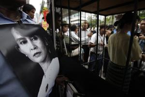 An anti-Myanmar government activist holds a poster showing Aung San Suu Kyi, as he and others gather for a demonstration on Monday. AP