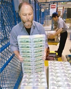 Red ink: A worker organizes dollar notes. The US borrows 50 cents of every dollar it spends. Glen E Ellman / Bloomberg