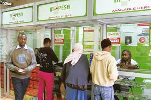 Customer connect: A man leaves an M-PESA booth after a money transaction in Nairobi. M-PESA, which has teamed up with Kenya Commercial Bank, has attracted one in six Kenyans in just over two years. Re