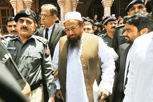 Back in action: A file photo of police escorting Hafiz Muhammad Saeed (in white cap) outside a court as he leaves after a hearing in Lahore. Saeed's release may heighten tensions between India and Pak