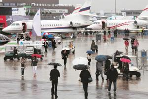 Rain-soaked: Visitors at the first day of the 48th Paris Air Show on Monday. The show comes at a time when the International Air Transport Association estimates sector losses this year could touch $9