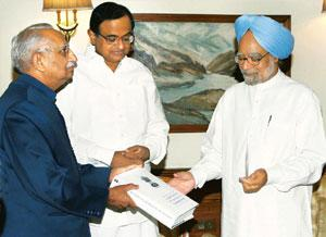 Job done: M.S. Liberhan (left) submits the Liberhan commission report to Prime Minister Manmohan Singh as home minister P. Chidambaram looks on in New Delhi on Tuesday.  Subhav Shukla / PTI