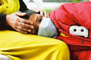 Pandemic scare: A boy suffering from fever rests in his mother's lap as he waits to be tested for the flu virus in Pune on Tuesday. Dhiraj Singh / AP