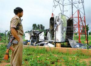 Scarred: Security personnel at the site of the blown-up mobile tower at Tukbera village in Palamu, Jharkhand. PTI