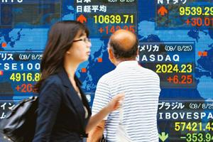 Modest gains: A man watches an electronic stock indicator in Tokyo, Japan, on Wednesday. Shizuo Kambayashi / AP