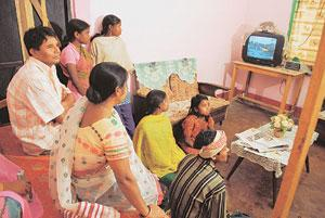 Reaching out: A file photo of a family and some labourers watching television in Kharonijan, a village in Jorhat, Assam. Broadcasters say measuring rural television audiences is a complex business. In