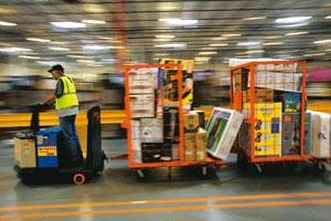 Inventory advantage: An Amazon employee in the Internet company's Phoenix warehouse. Amazon is shaking up retailers as it moves beyond books to its goal of becoming a Web-size general store. Jim Wilso