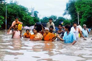 Submerged land: People wade through floodwaters to reach safer areas in Kurnool on Friday. At least 900,000 people in Andhra Pradesh and Karnataka have been shifted to relief camps. PTI