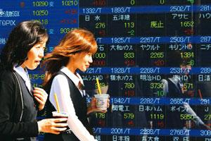 Markets slide: People pass a stock indicator in Tokyo. Japan's Nikkei declined 1.5% on Tuesday. Koji Sasahara/AP