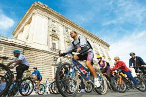 Urgent concern: Cyclists ride past the Royal Palace in Madrid on Sunday. Hundreds of cyclists took to the streets in the Spanish capital to highlight the need to act on the question of climate change.