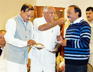 Making up: Karnataka CM B.S. Yeddyurappa (centre) offers sweets to dissident leader Janardhana Reddy (right) on Sunday. PTI