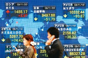 Strong market: People walking past a board showing stock prices in Tokyo on Friday. The Nikkei index ended 0.4% higher on Wednesday. Shizuo Kambayashi / AP