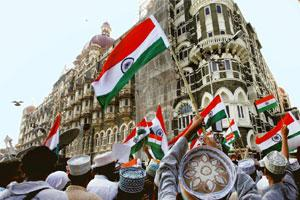 Seeking peace: People flaunt Indian flags outside the Taj Palace hotel on the first anniversary of the Mumbai terror attacks.Santosh Hirlekar / Mint