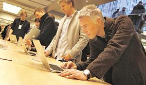 Gadget culture: Customers look at laptops at an Apple store in New York. Gadgets such as laptops and smart phones along with websites such as Twitter and Facebook have allowed people to always stay c