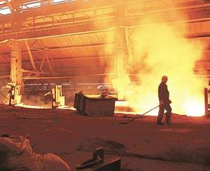 Firming up: A worker walks past a blast furnace at Tata Steel's Jamshedpur facility. While Tata has already raised prices by Rs2,000 a tonne, other private steel makers are also expected to increase r