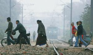 Services affected: People cross a railway track on a cold, foggy Sunday in New Delhi. Around 13 trains were cancelled on Sunday due to inordinate delays in preceding runs, Northern Railway officials s