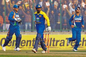 Profitable venture: A file photo of Indian cricket captain M.S. Dhoni (left) with Sri Lanka's Upul Tharanga during a match in New Delhi. Aijaz Rahi / AP