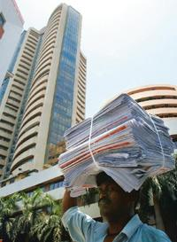 Market revival: A file photo of a man carrying share application forms in front of the Bombay Stock Exchange building in Mumbai. Indranil Mukherjee/AFP