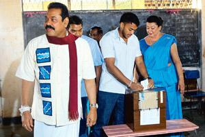 High expectations: Sri Lankan President Mahinda Rajapaksa (left) looks on as his son casts his vote at a polling booth near Madamulana, some 178km south of Colombo, on Tuesday. Rafiq Maqbool / AP
