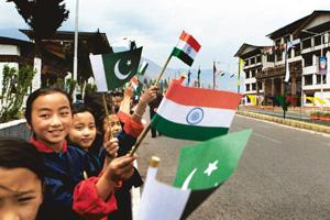 Regional pact: Bhutanese children wave flags of India and Pakistan as they await the arrival of Saarc dignitaries in Thimpu on Monday. Manish Swarup/AP