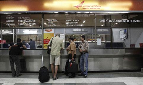 Stranded passengers stand outside the Air India counter at the domestic airport in New Delhi on Tuesday. Adnan Abidi / Reuters