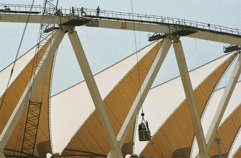 Money game: Workers look on as a crane lowers construction material at the under-renovation Jawaharlal Nehru Stadium in New Delhi, the main venue of Commonwealth Games 2010. Gurinder Osan/AP