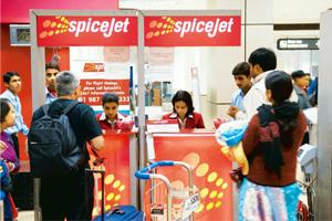 Safety check: Passengers queue at a SpiceJet counter at the Indira Gandhi International Airport in New Delhi. The carrier had deployed a 189-seat aircraft instead of a scheduled one with 212 seats on
