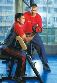 Pump up: Rajesh Desai, MD of Pro-Fit Functional Fitness Centre in Mumbai, supervises a client's routine. Kedar Bhat/Mint
