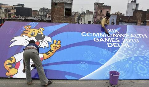Workers clean a billboard outside the Commonwealth Games athletes village in New Delhi on Wednesday. Parivartan Sharma / Reuters Photo