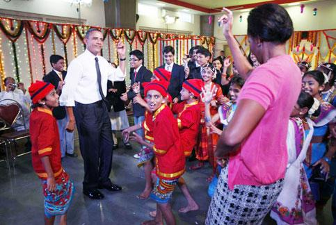 President Barack Obama and first lady Michelle Obama dance with students during a celebration of Diwali at Holy Name High School in Mumbai on Sunday. Charles Dharapak/ AP photo