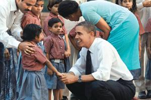 Time out: US President Barack Obama and First Lady Michelle Obama with the children of workers who carried out the renovation work at Humayun's Tomb, during a visit to the monument on Sunday. PTI