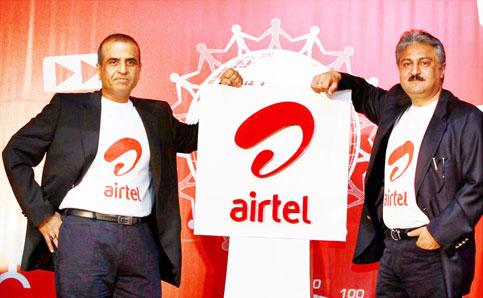 Bharti Airtel chairman and managing director Sunil Bharti Mittal and CEO (India and South Asia) Sanjay Kapoor pose with the company's new logo in New Delhi on Thursday. Kamal Kishore \ PTI photo