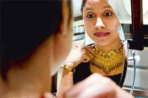 Perceptions of wealth: A woman tries out a gold necklace at a showroom on the outskirts of New Delhi. This was the decade that urban middle-class India began to slowly step out of the protection of go
