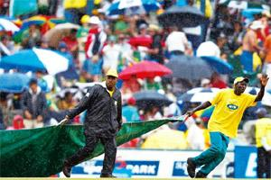 Washed out: Groundsmen cover the pitch as rain disrupts a match in South Africa. Siphiwe Sibeko/Reuters