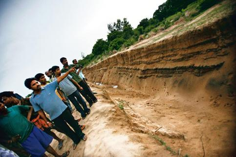 Impending development: On the land that has already been acquired by the state government, villagers and workers show the drain and a boundary wall being built at Polang for the Posco Steel project