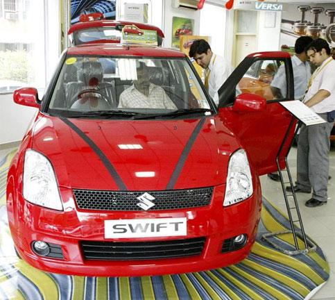 Customers look at the Maruti Suzuki Swift car at a showroom in New Delhi. Photo: Bloomberg