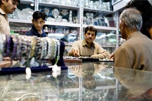 Sales staff at a jewelry shop wait for customers, in New Delhi. (File photo Bloomberg)