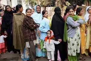 Women stand in line to cast vote. Photo: PTI