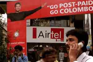 A mobile phone user passes an Airtel promotion. Photo: Bloomberg
