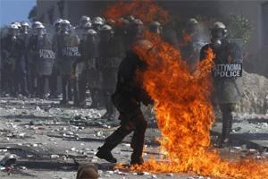 A Greek police officer is set partly on fire by an exploding petrol bomb, thrown by anti-austerity protesters, outside the parliament during clashes in Athens on Wednesday (Reuters)