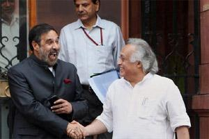 Union minister of commerce, industry & textiles Anand Sharma shakes hands with rural development minister Jairam Ramesh as they leave after attending a cabinet meeting at South Block in New Delhi