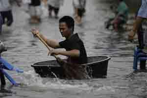 Thai uses a broom to paddle a big plastic container along a flooded street in Bangkok, Thailand. Photo: AP