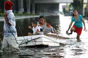 A family wades down a flooded street in Bangkok, Thailand. Photo: Bloomberg