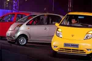 Tata Nano cars sit on stage during a news conference . Photo: Bloomberg