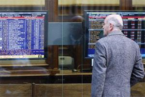 A man looks at a stock exchange board monitor outside a bank, in Milan, Italy. Photo: AP