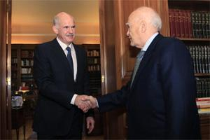 Greece's President Karolos Papoulias (R) shakes hands with Greek Prime Minister George Papandreou at his office inside the Presidential Palace in Athens