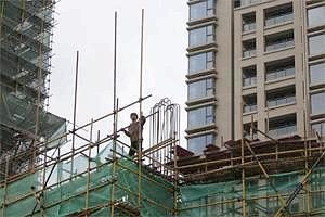 A construction worker stands on a scaffold in an area where old residential buildings are being demolished to make room for new skyscrapers in Shanghai (Reuters)