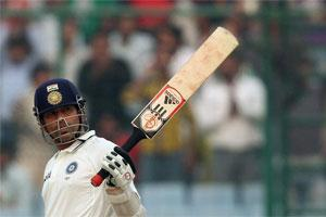 Sachin Tendulkar raises his bat in celebration after completing 15,000 runs in his test career.Photo: Reuters.