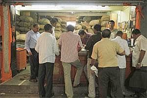 Customers wait in front of a spice retailer at a spice market in Mumbai